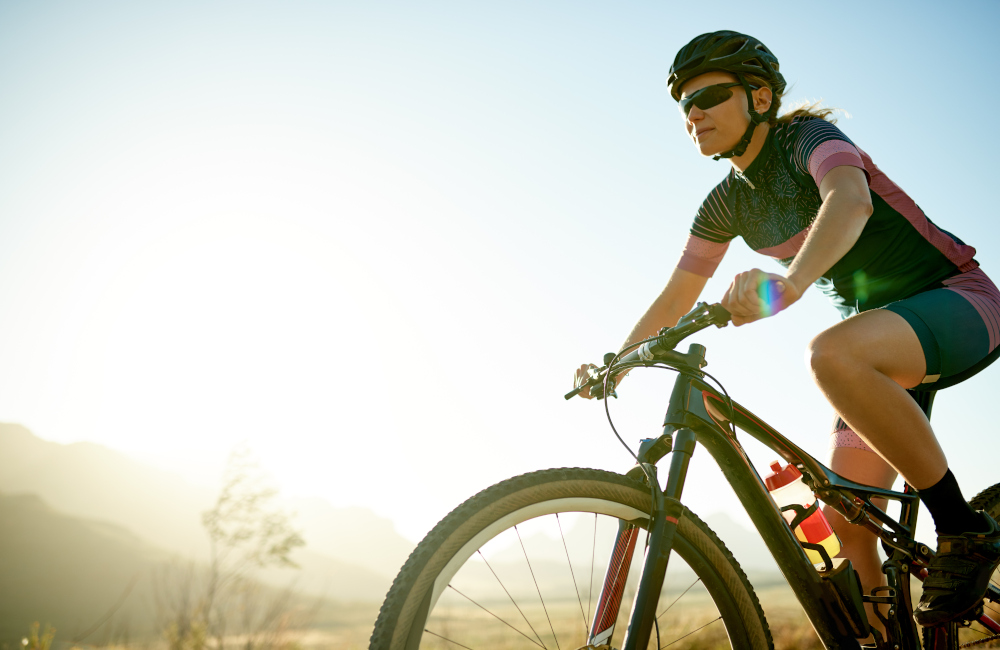 Shot of a sporty young woman out cycling on a country road